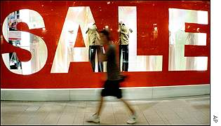 A woman walks past a shopping centre in Kuala Lumpur where a big SALE sign is displayed.