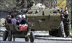 Ethnic Albanians pass a Macedonian armoured personnel carrier in Tetovo