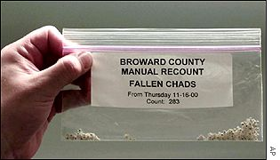 Electoral officials collect chads during the election recount