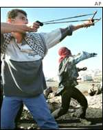 Palestinians firing sling shots at Israelis