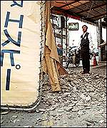 A shop sign and debris from a wall lie on the ground after the earthquake