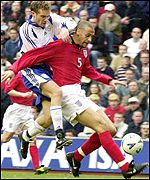 Rio Ferdinand holds off the challenge of Jonathan Johansson