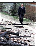 Ethnic Albanian teacher Izair Halili walks to his burned property in Gajre