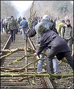 Protesters block the railway line with branches