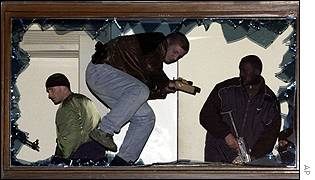 Police clamber through a broken window at the Milosevic residence