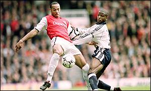 Thierry Henry and Alton Thelwell fight for the ball