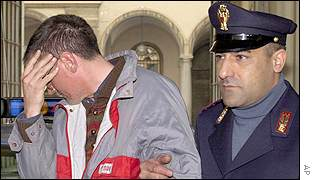 Policeman leads suspect Franco Rapelli to jail