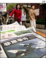 Shanghai locals pass a newspaper featuring news of the planes' collision