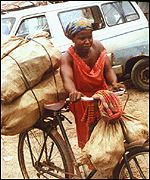 A rural Nigerian woman carries heavy loads on her bicycle