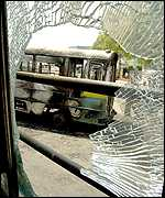 Destroyed bus seen through the smashed window of another