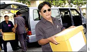 Workers carry boxes of Mr Thaksin's documents into the courthouse