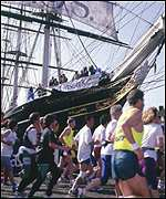 Cameras catch the action as runners pass the Cutty Sark