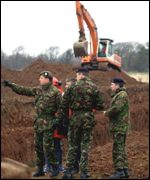 An army digger prepares a burial site