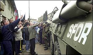 Bosnian Croats give the nationalist salute in Grude after protestors clashed with peacekeepers