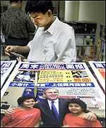 A Chinese stands near a copy of a magazine featuring President Bush