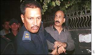 Mohammad Arshad Chima (right) is led away