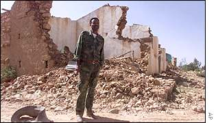 Eritrean soldier in front of destroyed building