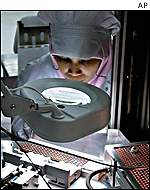 A Malaysian worker assembles an electronic component