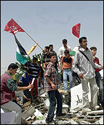 Palestinians protest on the rubble of a home shelled by Israel