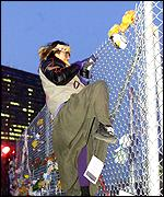 A protester tries to climb the security fence surrounding the summit area