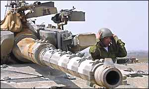 An Israeli tank commander watches Palestinian areas from his vehicle