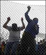 Protesters climb a chain link fence