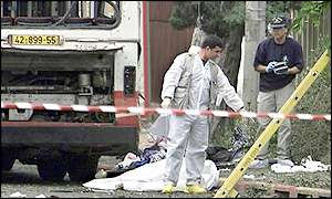 Israeli forensic police examine the area around the bombed bus