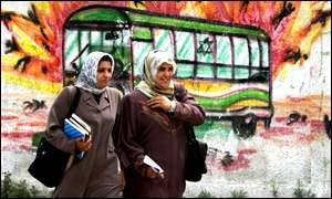 Palestinian women walk by graffiti depicting an exploding Israeli bus in Gaza City