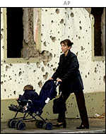 A Bosnian woman pushes her child in a pushchair past a wall covered with shrapnel holes