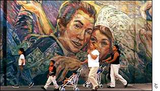 A Hispanic family walks past a mural in Los Angeles