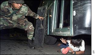 Soldier tries to get demonstrator out from under a bus