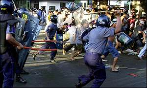 Riot police charge demonstrators with batons