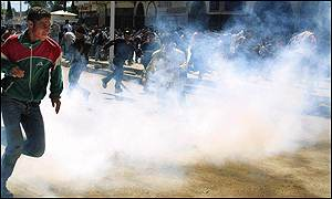 Demonstrators run away from tear gas fired by anti-riot police in Bejaia