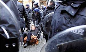 A protester is dragged away by riot police on Oxford Street