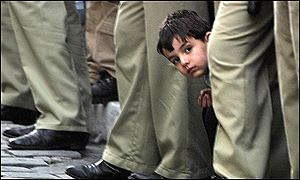 A boy peeps through the legs of Syrian police to get a look at the Pope