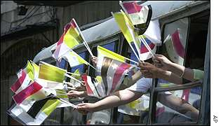 Wellwishers wave Vatican and Syrian flags from a bus in Damascus