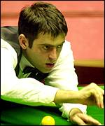 Ronnie O'Sullivan stretches for a shot