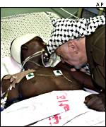 Yasser Arafat visits a wounded Palestinian child