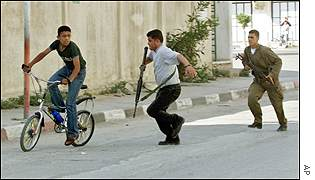Palestinian police and civilians run as Israeli helicopters rocket the Palestinian police headquarters