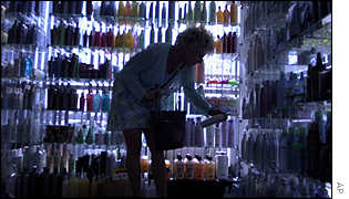 Woman looks for hair products with the help of window light in a Californian shop