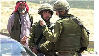 Israeli troops stopping drivers at a checkpoint