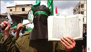 A masked Palestinian man marches with a handgun and the Koran, the Muslim holy book