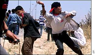 Palestinian youths pelt Israeli soldiers with stones during clashes at a Jewish settlement