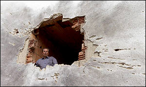 Ethnic Albanian man looks through a hole in a wall of his house caused by a shell