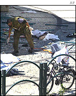 Israeli police search the scene of a suicide bomb attack