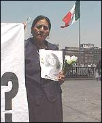 A mother holds a photo of the daughter she says disappeared in police custody