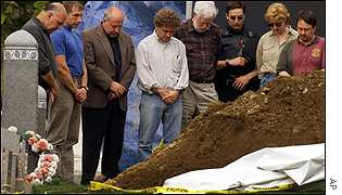 Researchers pray over the grave of an unidentified child victim