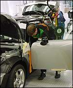 Worker fitting a door on a Mini