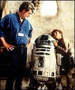 George Lucas looks on as Jake Lloyd listens to R2D2