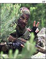 A Serbian special police team member flashes a three finger salute while approaching a former Albanian rebel stronghold